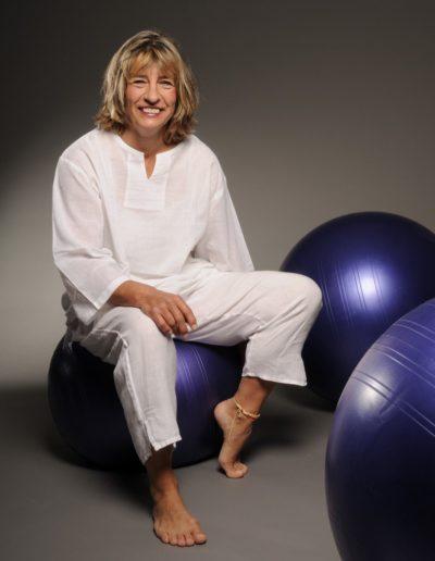 Eine Frau mit blonden Haaren ist ganz in weiss gekleidet und sitzt auf einem violetten Gymnastikball. An ihrem linken Fuss trägt sie eine Fusskette. Je ein weiterer Gymnastikball ist rechts hinter und vor ihr.