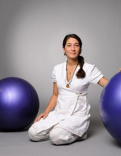 Eine Frau mit einem dunklen Zopf ist ganz in weiss gekleidet schaut direkt in die Kameralinse. Dazu trägt sie eine lange Kette. Ihre linke Hand hat sie auf einem violetten Gymnastikball. Im Hintergrund ist ein zweiter Gymnastikball.