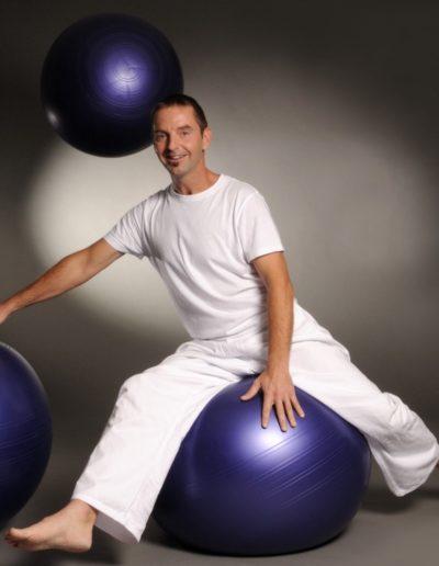 Ein Mann mit dunklen kurzen Haaren und ganz in weiss gekleidet sitzt auf einem violetten Gymnastikball. Dabei geht ein Bein nach hinten und das Andere nach vorne. Seine rechte Hand hat er auf einem zweiten Ball abgestützt. Ein dritter Ball fliegt hinten durch die Luft.