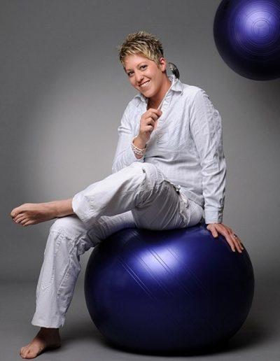 Eine Frau mit kurzen, blonden Haaren ganz in weiss gekleidet sitzt auf einem violetten Gymnastikball. In ihrer rechten Hand hält sie eine silberne Suppenkelle. Im Hintergrund fliegt ein weiterer Ball durch die Luft.