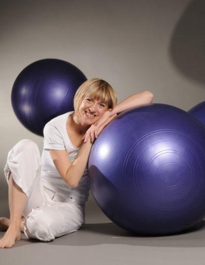 Eine Frau mit blonden Haaren und ganz in weiss gekleidet lehnt sich an einem violetten Gymnastikball an. Im Hintergrund sind zwei weitere Gymnastikbälle: Einer links in der Luft, der Andere rechts am Boden.