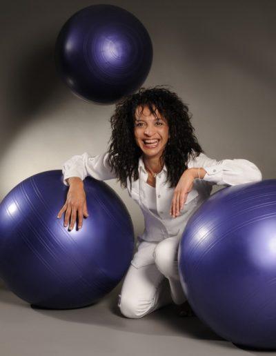 Eine Frau mit dunklen Locken stützt sich lachend mit ihren Armen auf je einem violetten Gymnastikball ab. Dahinter ist ein weiterer Ball in der Luft. Dazu ist die Frau ganz in weiss gekleidet.