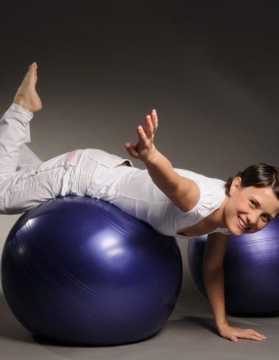Eine Frau mit dunklen, kurzen Haaren und ganz in weiss gekleidet liegt mit dem Bauch nach unten auf einem violetten Gymnastikball. Sie stützt sich mit einer Hand auf dem Boden ab, während die zweite Hand und Füsse in der Luft sind. Dahinter ist noch ein Ball.