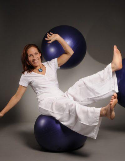Eine Frau, ganz in weiss gekleidet sitzt auf einem violettem Gymnastikball. Ihre Hände und Füsse hat sie vom Boden abgehoben. Sie hat rötliche Haare und trägt eine Kette mit einem runden blauem Anhänger. Im Hintergrund sind zwei weitere Gymnastikbälle.