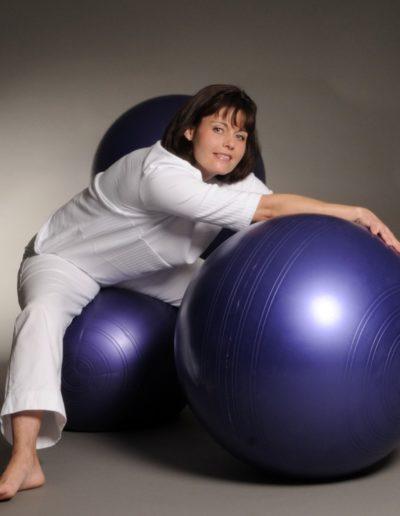 Eine Frau mit mittellangen dunklen Haaren und in weiss gekleidet sitzt auf einem violetten Gymnastikball. Nach vorne gebeugt stützt sie sich auf einem weiteren Ball ab. Im Hintergrund fliegt ein dritter Ball durch die Luft.
