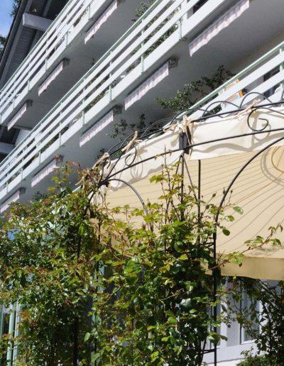 Am Ecken des Revital-Hauptgebäudes steht der Pavillon. Er besteht aus dünnen schwarzen geschwungenen Metallstäben. Dazwischen wachsen weisse Rosenranken.