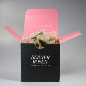 Eine quadratische Schachtel mit Teebeutel darin. Aussen ist sie schwarz, innen pink.