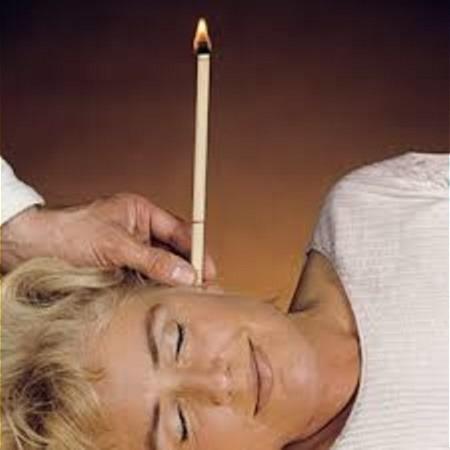 Eine Frau liegt auf der rechten Seite mit dem Gesicht nach vorne. Ihre Augen sind geschlossen. Eine weitere Person hält eine Ohrenkerze die im Ohr der Frau ist. Die dünne Kerze brennt.
