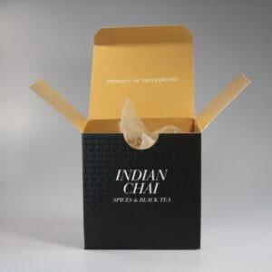 Eine quadratische Schachtel mit Teebeutel darin. Aussen ist sie schwarz, innen beige.