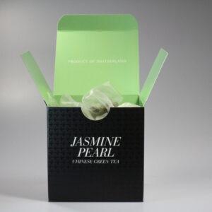 Eine quadratische Schachtel mit Teebeutel darin. Aussen ist sie schwarz, innen hellgrün.