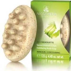 An der grünen Verpackungsschachtel lehnt eine ovale Massageseife an.