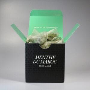 Eine quadratische Schachtel mit Teebeutel darin. Aussen ist sie schwarz, innen mintgrün.