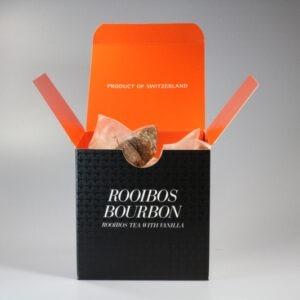 Eine quadratische Schachtel mit Teebeutel darin. Aussen ist sie schwarz, innen orange.