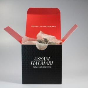 Eine quadratische Schachtel mit Teebeutel darin. Aussen ist sie schwarz, innen rot.