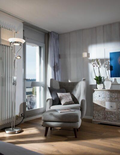 Vom Bettende her sieht man links die offene Balkontüre, ein Radiator daneben und eine Stehlampe davor. Im linken Ecken steht ein Ohrensessel mit 2 Kissen und daneben eine Kommode mit 12 Schubladen, einer Orchidee darauf und einem Bild darüber.