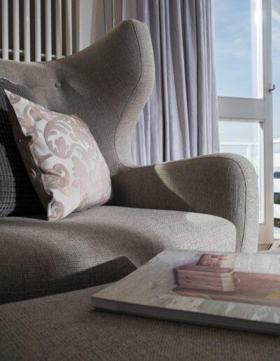 Links an der Wand neben der offenen Balkontüre befindet sich ein grosser Ohrensessel mit Fussteil. Auf dem Sessel sind zwei Kissen und auf dem Fussteil ein Magazin vom Revital.