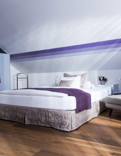 Ein Bild von einem Hotelzimmer. Links ist ein hellvioletter Einbauschrank. Rechts davon steht ein grosses Doppelbett mit Nachttischchen. Anschliessend ist ein grauer Sessel mit Fussteil und Stehlampe.