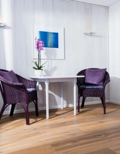 An einer grauen Bretterwand steht unter einem Bild ein weisser Tisch. Darauf steht eine Orchidee in einem weissen Topf. Auf beiden Seiten des Tisches steht jeweils ein Stuhl. An der rechten Wand hängt ein Spiegel und auf der linken Seite geht's auf den Balkon.
