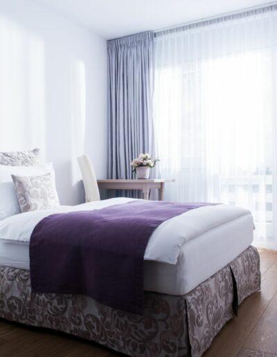 Ein kurzer Gang führt an einem Eckschrank zum Einzelbett des Zimmers an der linken Wand. Dahinter steht ein Tisch mit einem Stuhl vor dem Fenster und der Balkontüre. Rechts neben dem Fenster befindet sich eine Stehlampe.