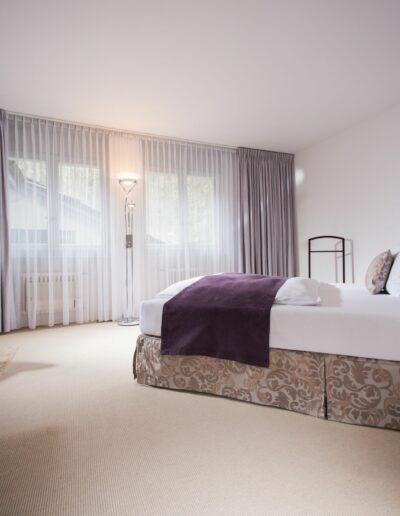 Von der Türe aus Fotografiert sieht man ein Tisch mit einem Stuhl an der linken Wand. Dahinter ist die Toilettentür. Auf der rechten Seite ist das Doppelbett mit dem Kopfende gegen die Wand. Vom Bett her geht der Blick aus den zwei Fenstern mit durchsichtigen Vorhängen davor.