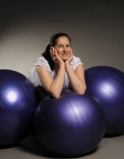 Eine Frau mit dunklen Haaren und in weiss gekleidet, stützt sich vorne auf einem violettem Gymnastikball ab. Links und rechts von ihr sind zwei weitere Gymnastikbälle.