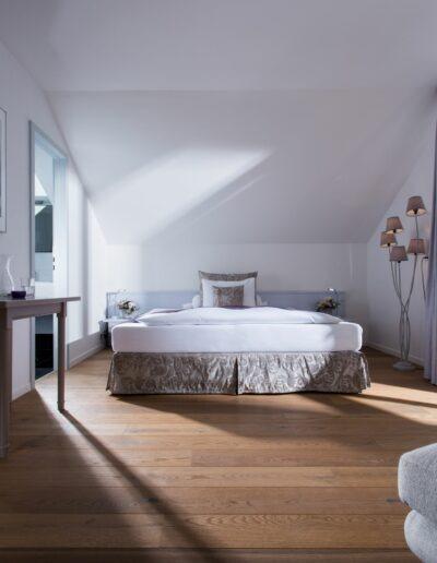 Im Hotelzimmer steht ein grosses Doppelbett hinten an der Wand. Vorne links steht ein Abstelltisch mit einer runden, weissen Vase mit Orchideen darin. Rechts führt eine Türe auf den Balkon. Vorne rechts ist ein grauer Sessel.