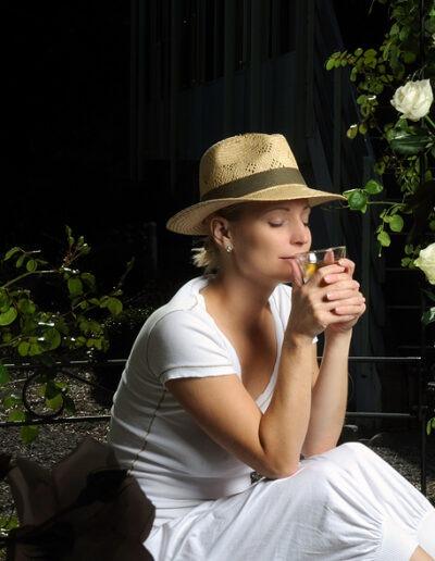 Eine Frau in weiss gekleidet und mit einem eleganten Strohhut sitzt in einem Pavillion. Dieser ist mit weissen Rosen überwachsen. Die Frau hat die Augen geschlossen und geniesst eine Tasse Tee.