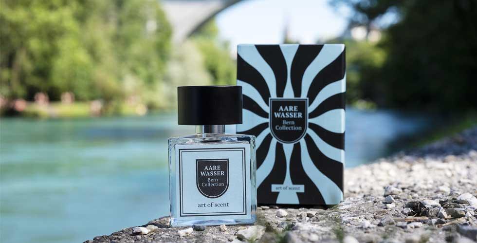 Eine Aufnahme der Stadt Bern. Auf einem Steinweg neben der grünen Aare steht die Verpackung des Parfums Aarewasser. Davor steht die Parfümflasche.