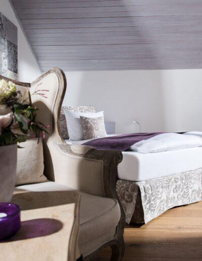 Das Bett ist diagonal von der hinteren linken Ecke in den Raum gestellt. Auf der rechten Seite steht mit ein wenig Abstand ein Tisch mit einer Orchidee im Topf und ein Stuhl. Vorne links steht ein weiter Tisch mit einem Ohrensessel dahinter.