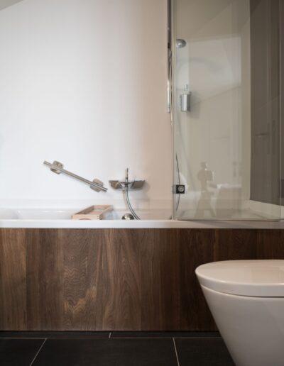Im Badezimmer ist die Toilette an der rechten Wand. Das Lavabo steht der Toilette gegenüber an der linken Wand. Hinten ist die Badewanne.