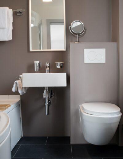 Links an der Wand befindet sich die Badewanne mit einem Wasserschutz aus Plexiglas. Rechts daneben das Lavabo mit anschliessendem WC. Über dem Lavabo hängt ein Spiegel.