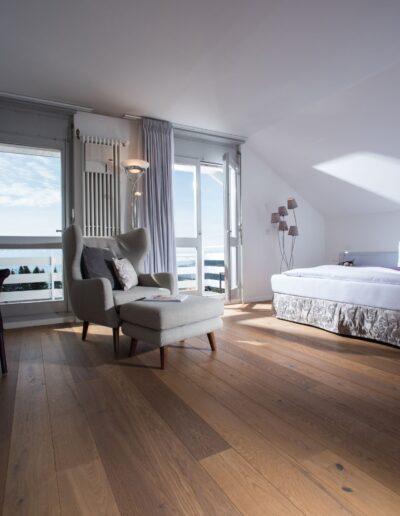 Im Zimmer steht links an der Wand ein Tisch mit zwei Stühlen. Hinten in der Mitte steht ein Sessel mit Fussteil zwischen Fenster und Balkontür. Auf der rechten Seite befindet sich das grosse Doppelbett.