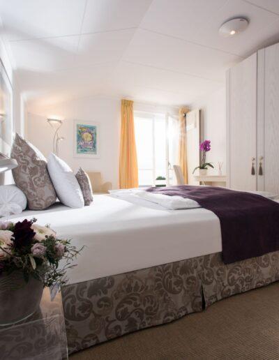 Vorne links steht ein gläsernes Nachttischchen mit einer Lampe und Blume darauf. Dahinter, mit dem Kopf gegen die linke Wand, steht das grosse Doppelbett. Am Fussende steht mit ein bisschen Raum dazwischen ein Einbauschrank. Die Balkontüre hinter dem Bett ist geöffnet.