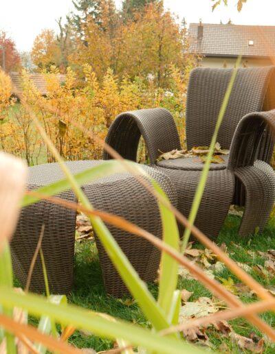 Ein Gartensessel mit Tisch steht zwischen einer herbstfarbenen Hecke und einem Baum. Auf dem Gras liegen heruntergefallene Blätter.