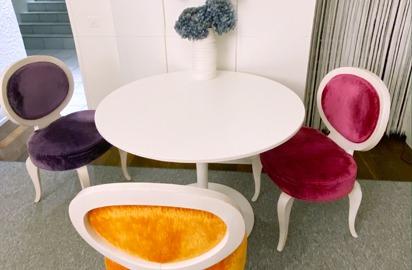 Ein weisser, runder Tisch an der Wand. Dazu stehen drei Stühle. Jeder davon hat eine andere Farbe: Fuchsia, Violett und Orange.