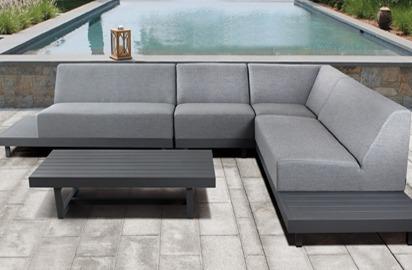 Eine graue Gartenlounge mit einem dunkelgrauen Loungetisch auf einer Terrasse. Dahinter befindet sich ein Pool und auf dem Poolrand eine Holzlaterne.
