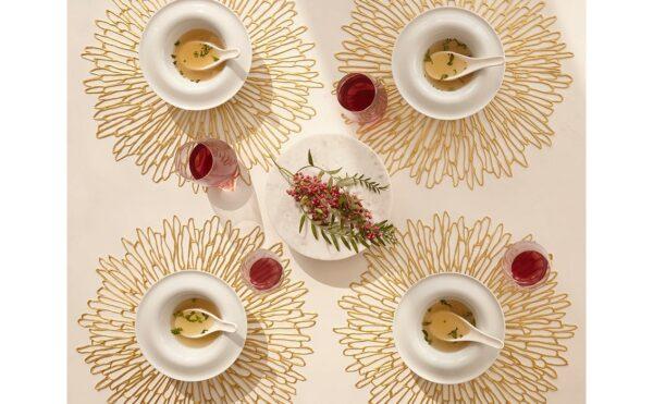 Vier flexible, durchbrochene Tischsets mit jeweils einer Suppe und Glas darauf. In der Mitte ist eine Platte mit einer Blätterdekoration darauf.