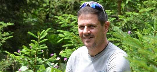 Yves Giroud sitzt mit einem grauen Tshirt zwischen Tannen. Er hat kurze, graue Haare und eine Sonnenbrille auf dem Kopf.