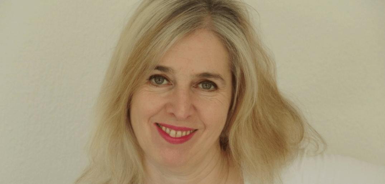 Ein Portraitfoto von Mona Grigolo vor einer weissen Wand. Sie hat offene, blonde Haare, helle Haut und rote Lippen. Dazu trägt sie ein leichtes, weisses Shirt mit Muster um den Ausschnitt.