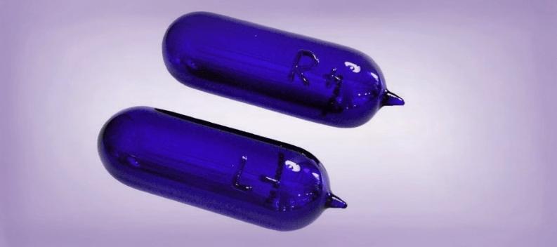 Auf weissem Hintergrund sind zwei ovalförmige Glaskapseln aus blauem Pyrexglas. An einem Ende haben sie eine kleine Spitze. Diese sind mit Resonanzmustern geladen.